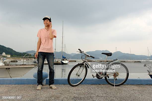 teenage boy (17-19) using mobile phone at waterfront - yonago stock photos and pictures