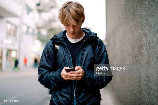 teenage boy using mobile phone while walking on sidewalk against wall in city - boys stock pictures, royalty-free photos & images