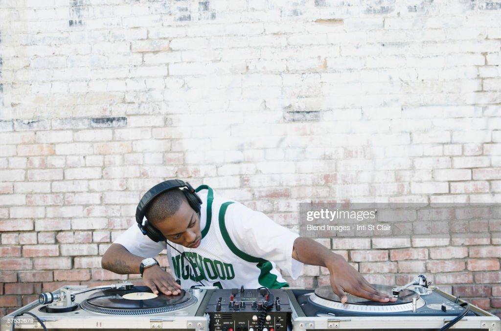 Teenage boy using turntables and headphones : Stock Photo