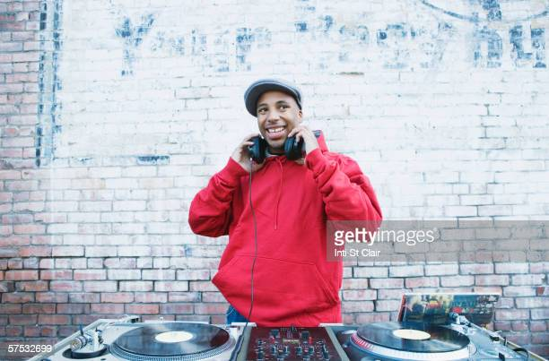 teenage boy using turntables and headphones - dj photos et images de collection