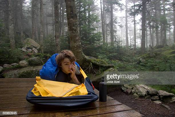a teenage boy wakes up in a wilderness campsite. - appalachian trail stock photos and pictures