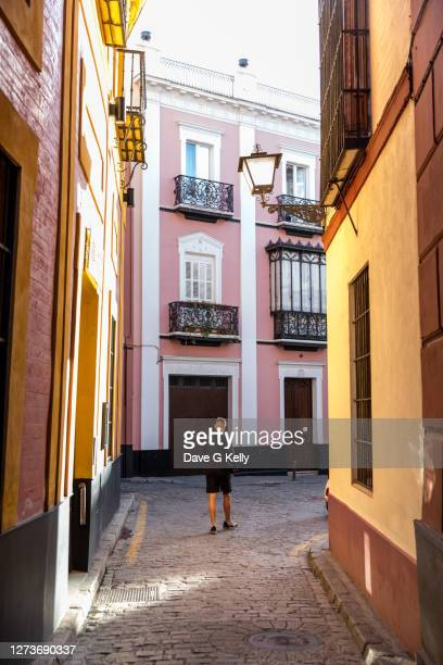 teenage boy walking down narrow spanish street - seville stock pictures, royalty-free photos & images