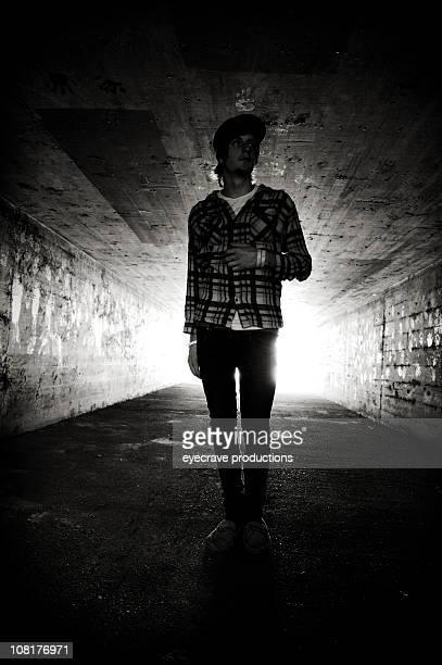 Teenage Boy Walking Down Tunnel, Black and White