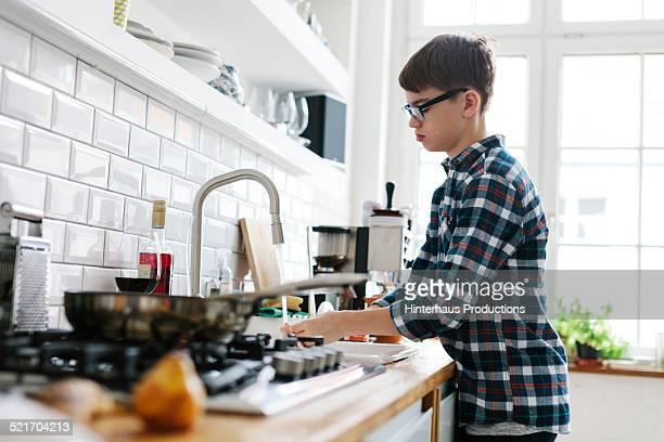 Teenage boy washing up in the Kitchen