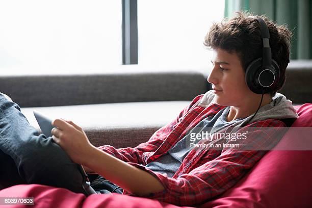 Teenage boy watching a digital tablet at home.