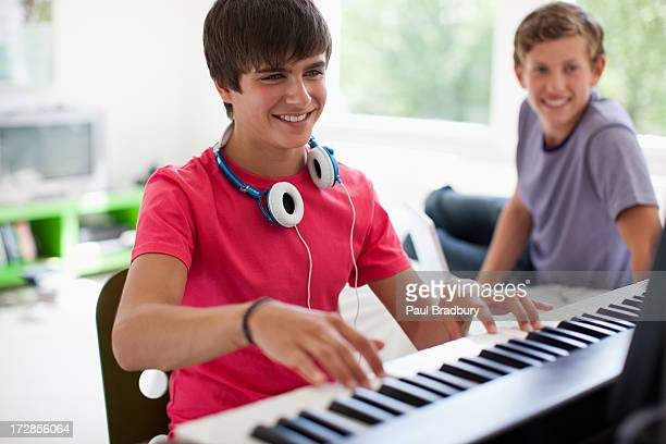 teenage boy watching friend play electronic piano keyboard - keyboard player stock photos and pictures