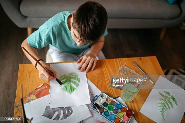 teenage boy watercolor painting while sitting on floor in living room - painting stock pictures, royalty-free photos & images