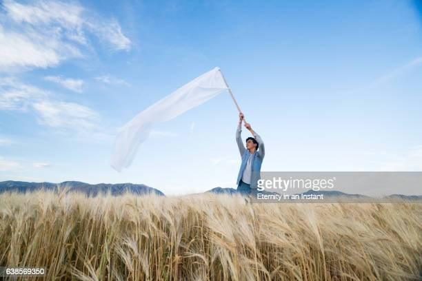 Teenage boy waving a big white flag in a wheat field