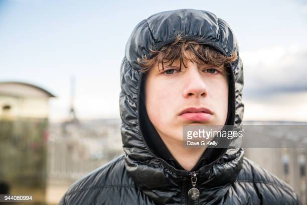 teenage boy wearing a hood paris cityscape background - boredom stock pictures, royalty-free photos & images
