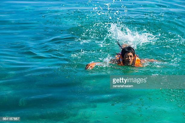 Teenage boy wearing a life jacket swimming in the sea, Salakan Island, Semporna, Sabah, Malaysia