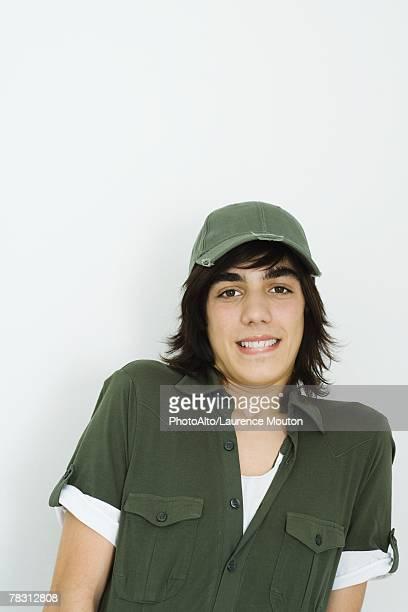 Teenage boy wearing baseball cap, biting lip, looking at camera