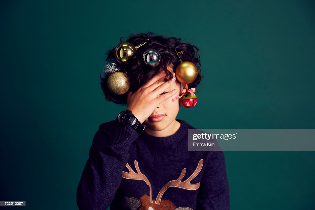 18c7efaa252 Teenage Boy Wearing Christmas Jumper And Baubles In Hair Covering ...