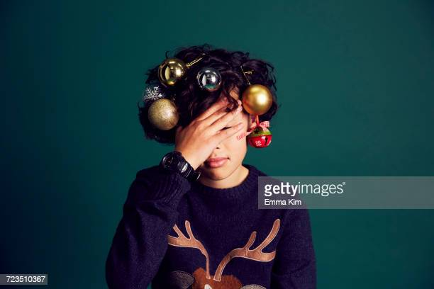 teenage boy wearing christmas jumper, and baubles in hair, covering face with hand - christmas jumper fotografías e imágenes de stock