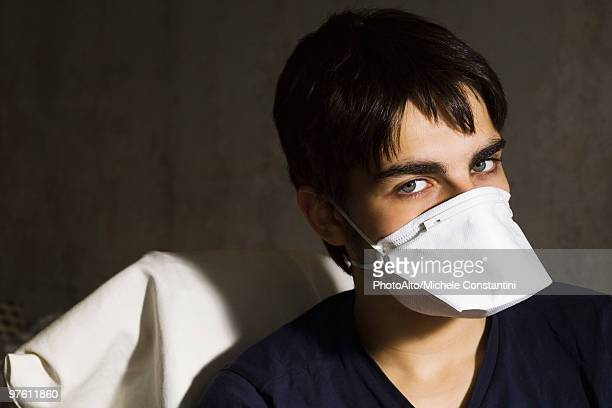 teenage boy wearing flu mask, looking at camera - flu mask stock photos and pictures
