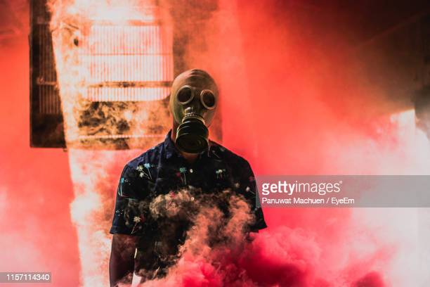 teenage boy wearing gas mask while standing amidst smoke - gas mask stock pictures, royalty-free photos & images