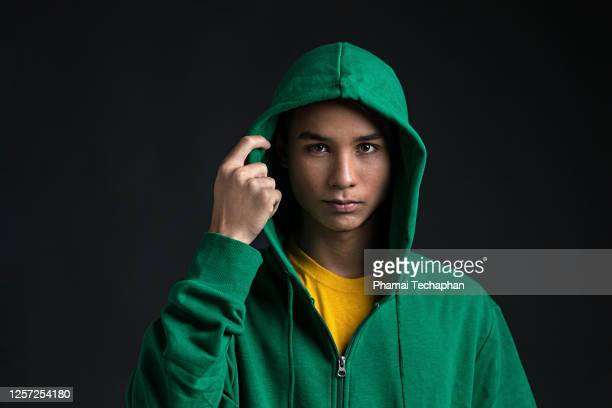 teenage boy wearing green hoodie - hooded top stock pictures, royalty-free photos & images