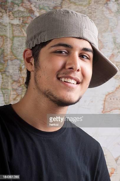 A teenage boy wearing his grey hat sideways