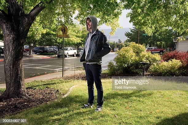 Teenage boy (18-20) wearing hooded sweatshirt on front lawn, autumn