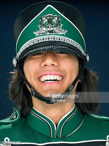 Teenage boy (16-18) wearing marching band uniform, smiling, portrait