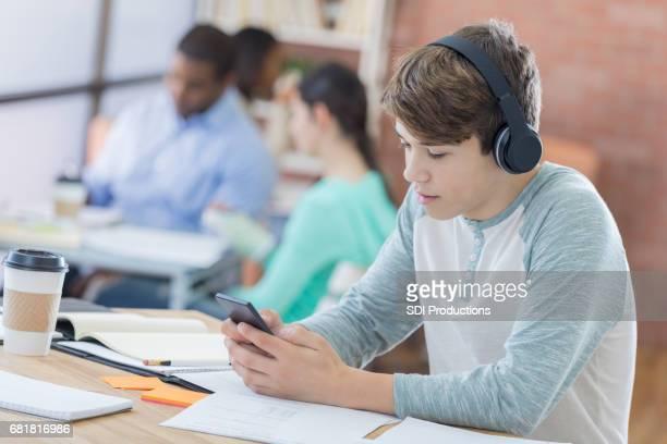 Teenage boy wearing wireless headphones at school