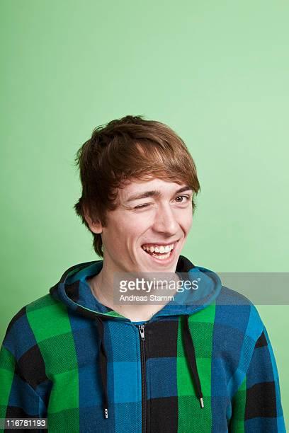 a teenage boy winking playfully, portrait, studio shot - 18 19 jahre stock-fotos und bilder
