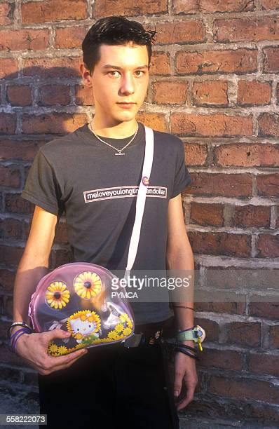 A teenage boy with a childrens plastic handbag at Machesters annual Mardi Gras gay event Canal Street Manchester UK 2003