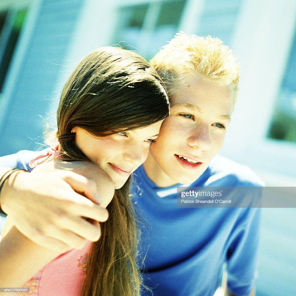 Teenage boy with arm around teenage girl, outside : Stockfoto