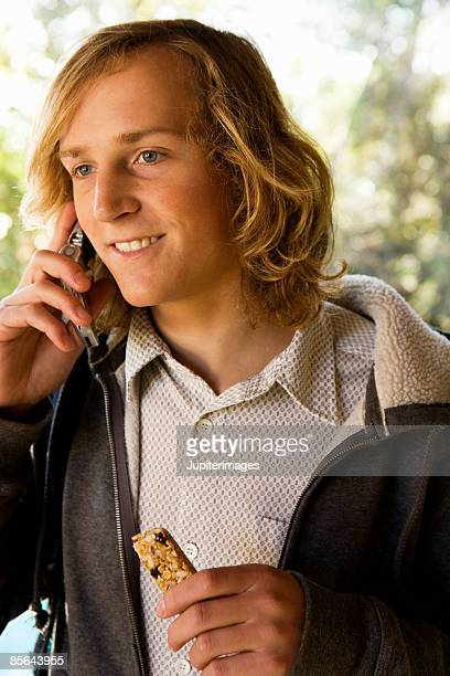 Teenage boy with cell phone and granola bar