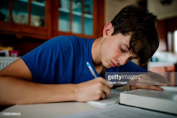 teenage boy with cochlear implant doing homework - cochlear implant stock pictures, royalty-free photos & images