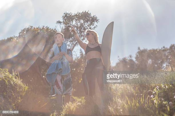 Teenage boy with down syndrome and woman with surfboard at the coast