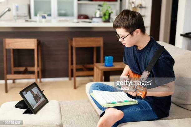 adolescente con sindrome di down che prende lezioni di musica da apprendimento a distanza a casa su internet - disabilitycollection foto e immagini stock
