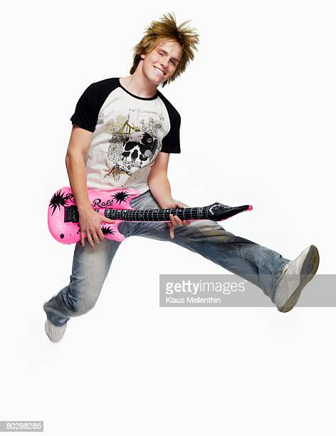 Teenage boy (16-17) jumping with toy guitar, smiling, portrait