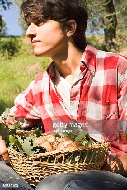 Teenage boy with fresh produce basket , Italy