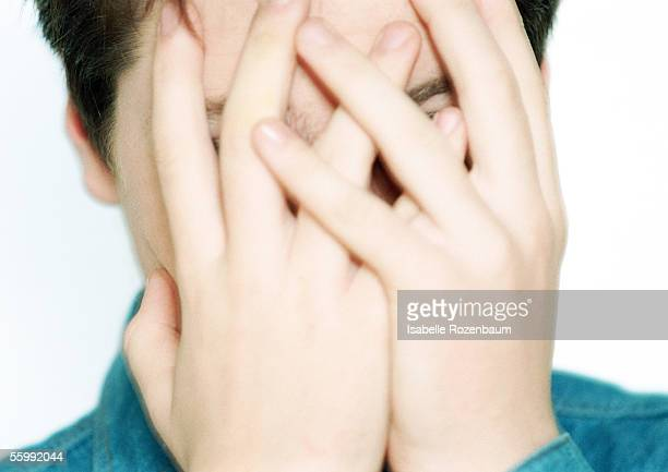 Teenage boy with hands covering face, close-up