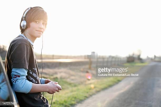 Teenage boy with headphones by car