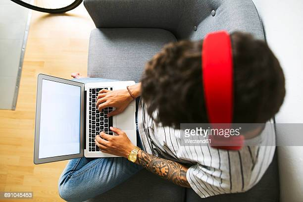 Teenage boy with headphones sitting on couch at home using laptop, top view