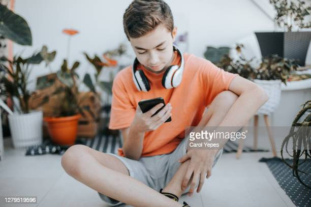 teenage boy with headphones using mobile phone at table in room. 11 years old boy sitting behind a laptop and listening to music with headphones or playing video game. - 12 13 years stock pictures, royalty-free photos & images