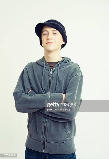 Teenage boy with his arms crossed wearing a black hat