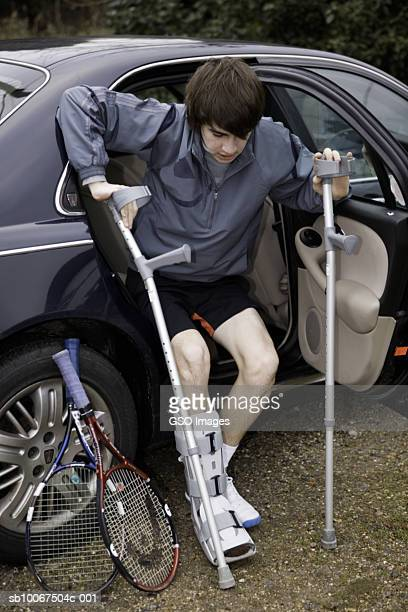 Teenage boy (16-17) with leg in cast getting out of car