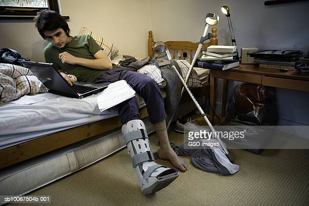 Teenage boy (16-17) with leg in cast sitting on bed using laptop