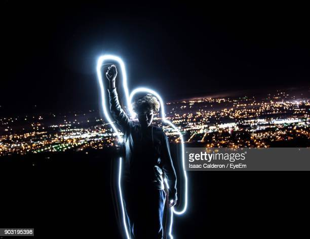 teenage boy with light painting standing against cityscape at night - lichtmalerei stock-fotos und bilder