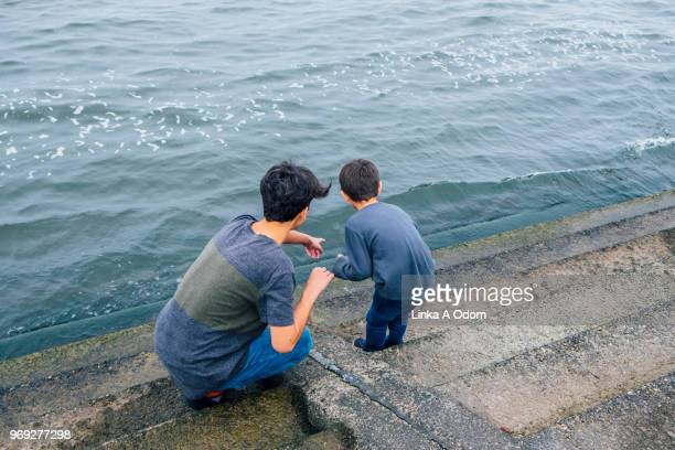 Teenage Boy with Little Brother next to large body of Water