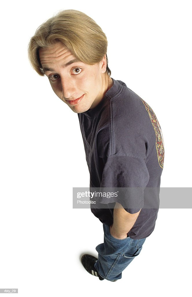 teenage boy with longer dark blonde hair and brown eyes wearing a purple t-shirt blue jeans and black soccer shoes looks up into the camera with big eyes and a slight smile and raises his eyebrows : Stockfoto
