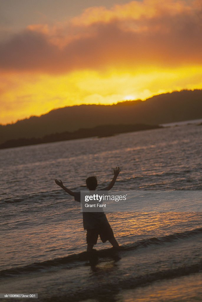 Teenage boy (14-15) with raised arms, standing on beach at sunset, rear view : Stockfoto