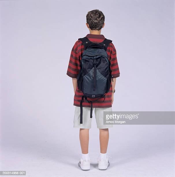 Teenage boy (14-15) with rucksack, posing in studio
