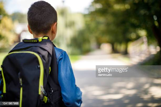 teenage boy with school bag going home from school - rucksack stock pictures, royalty-free photos & images