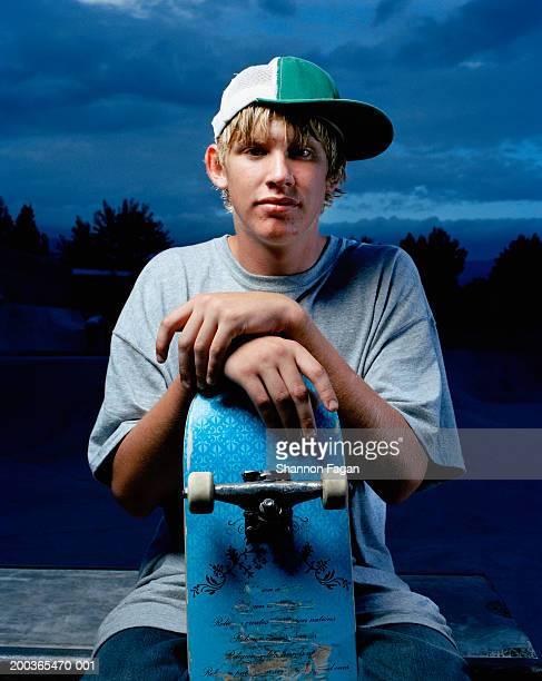 Teenage boy (14-16) with skateboard, portrait
