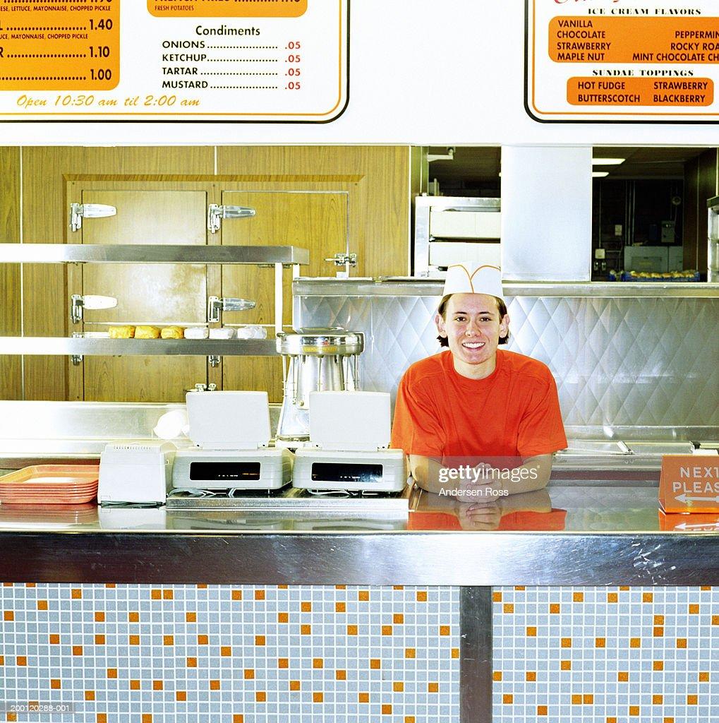 Teenage boy (17-19) working behind counter of fast-food restaurant : Stock-Foto