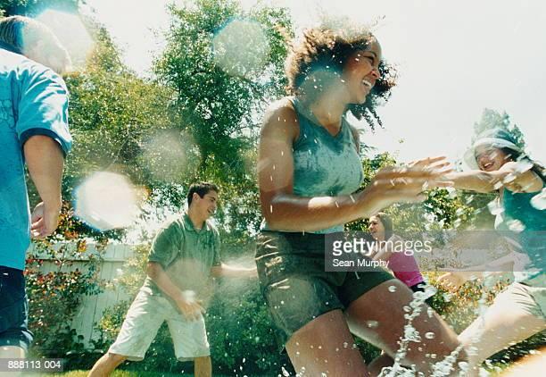 teenage boys and girls (14-16) outdoors getting wet with hose - seulement des adolescents ou adolescentes photos et images de collection