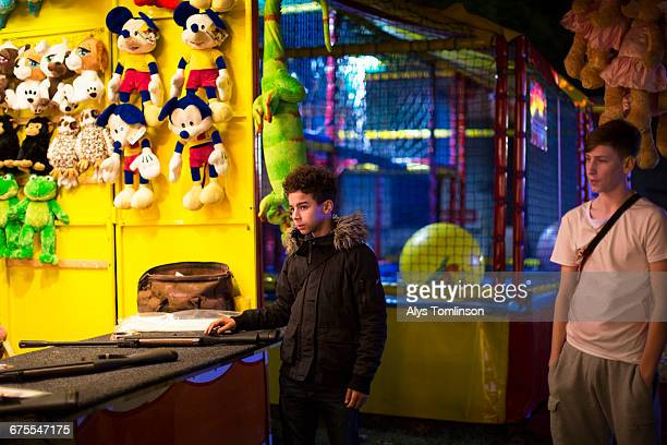 teenage boys at a fairground stall at night